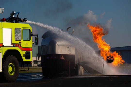A Naples Airport Authority fire engine extinguishes a simulated airplane fire during a disaster training exercise, Wednesday, Oct. 16, 2019, at the Naples Airport.