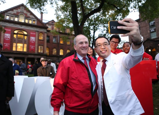 "Rutgers President Robert Barchi takes selfies with Pharmacy student Alexander K. Lo  in front of the donated gift from Johnson and Johnson, the ""Revolutionary"" sign, during Rutgers' 250th anniversary celebration in November 2015."