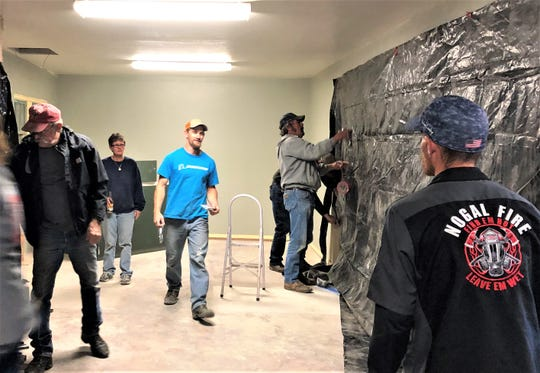 Members of the Nogal Volunteer Fire Department begin blacking out walls Tuesday in the haunted house-to-be in midtown Ruidoso.