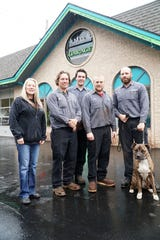 The staff at Downtown Garage in Milford is working on donating a vehicle to a needy family. From left are owner Karen Wielkopolan, son John Wielkopolan, Nick Streng, Jake Roberts, Robert Theisen, and shop-dog Rowdy.