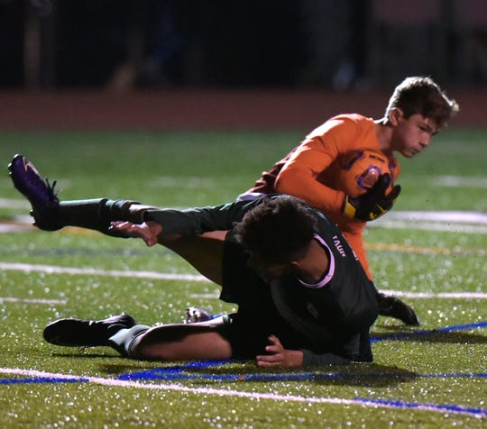 As a Novi Wildcat crashes to the turf near him, Farmington's goalie Steve Ihm holds onto the ball.