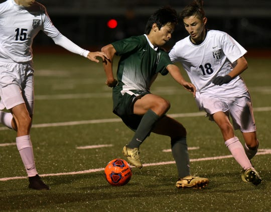Novi's Shion Soga, center, plays the ball.