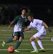 Novi Wildcat Taiga Shiokawa passes the ball to teammate near the Farmington net.