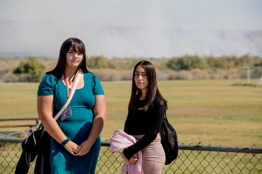 From left, Miranda Lopez and Kimberly Arellano, both juniors at Desert Mirage High School, were part of a group of students who wrote letters to school board members, local, state and federal officials telling them how smoke from a nearby dump affected them at school. Rep. Raul Ruiz, D-Palm Desert, commended the activism by students, saying it played a pivotal role in the decision to shut down the Sun Valley Recycling Center, which has had recurring mulch fires. The pair were photographed at their school as the smoke is visible in the background.