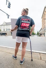 Jeanne Showalter holds a sign during the Don't Punish Pain rally in downtown Pensacola on Wednesday.