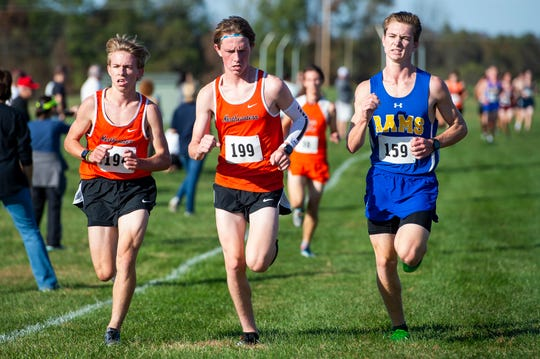 (From left) Northeastern's James Herman and Cole Perry (199) run alongside Kennard-Dale's Collin Wolf (159) in the YAIAA cross country championships at Gettysburg Area High School on Tuesday, October 15, 2019.