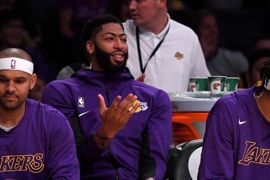Los Angeles Lakers forward Anthony Davis gestures as he sits on the bench during the second half of a preseason against the Golden State Warriors NBA basketball game Monday, Oct. 14, 2019, in Los Angeles. The Lakers won 104-98. (AP Photo/Mark J. Terrill)