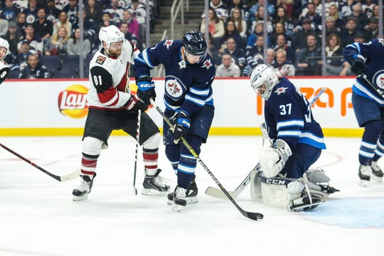Oct 15, 2019; Winnipeg, Manitoba, CAN; Winnipeg Jets defenseman Dmitry Kulikov (7) clears the rebound away from Arizona Coyotes forward Phil Kessel (81) during the first period at Bell MTS Place. Mandatory Credit: Terrence Lee-USA TODAY Sports