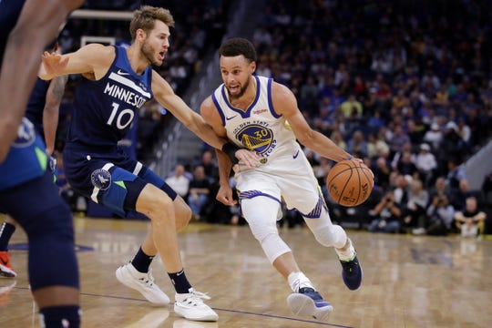 Golden State Warriors' Stephen Curry, right, drives the ball against Minnesota Timberwolves' Jake Layman (10) during the first half of an NBA preseason basketball game Thursday, Oct. 10, 2019, in San Francisco. (AP Photo/Ben Margot)