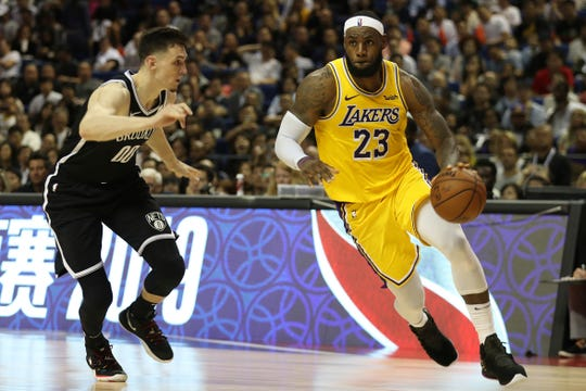 Los Angeles Lakers' Lebron James, right, drives against Brooklyn Nets' Rodions Kurucs, left, during their preseason NBA game in Shanghai, China, Thursday, Oct. 10, 2019.
