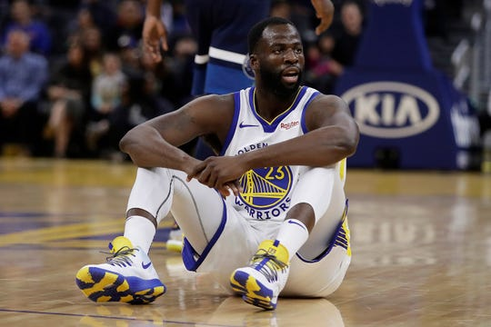Golden State Warriors' Draymond Green watches from the floor during the first half of the team's NBA preseason basketball game against the Minnesota Timberwolves on Thursday, Oct. 10, 2019, in San Francisco. (AP Photo/Ben Margot)