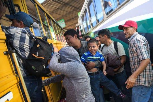 Varios migrantes salvadoreños se trepan a un autobús.