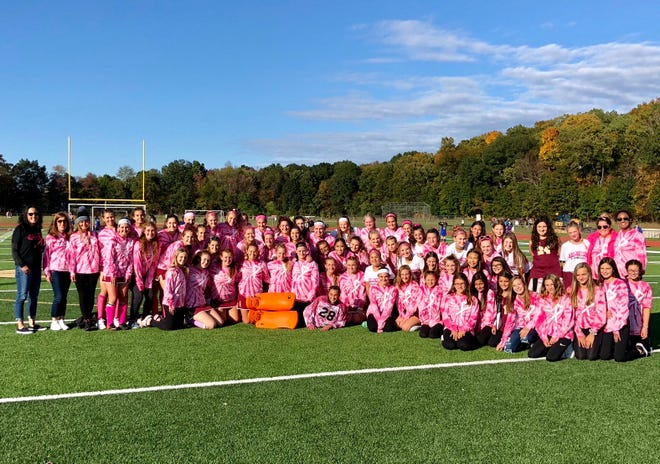 The Arlington field hockey team poses after its 12th annual Miles of Hope game, which raises money to be donated to the breast cancer foundation.