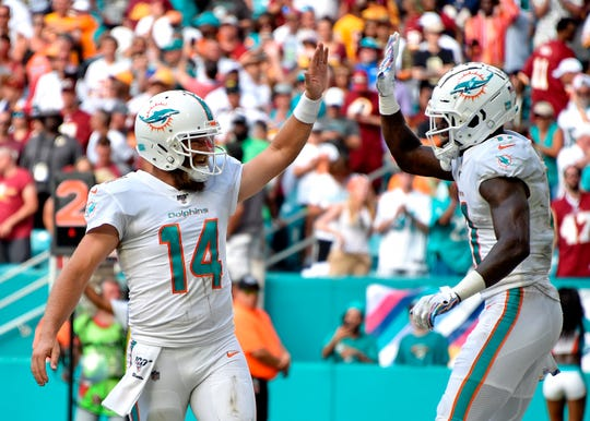 Miami Dolphins quarterback Ryan Fitzpatrick, left, greets wide receiver DeVante Parker after a touchdown catch against the Washington Redskins.