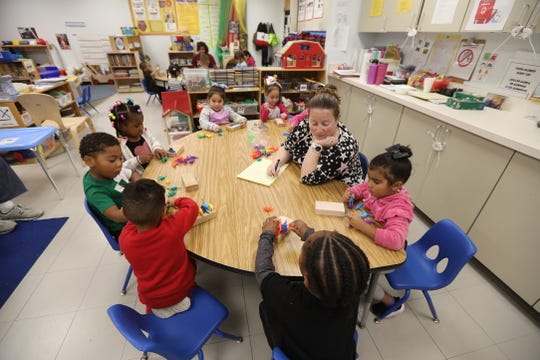 Jennifer Roy, a universal prekindergarten teacher at Ibero Early Childhood Services, listens as each child takes a turn at counting their dinosaurs.