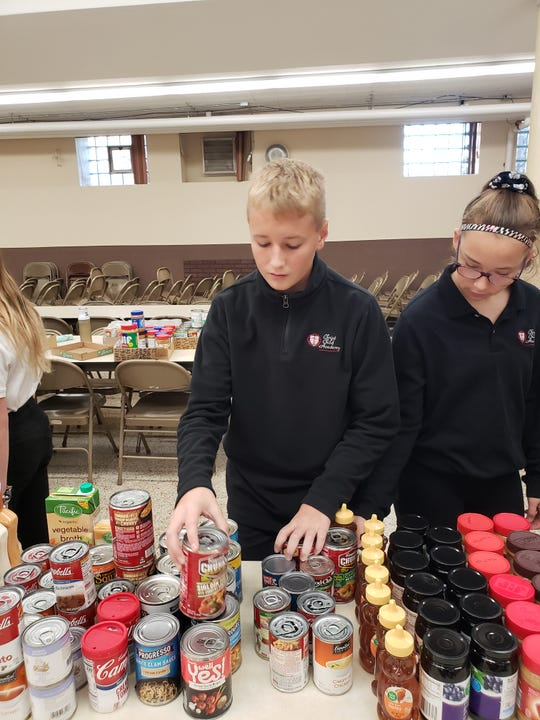 Students from the Christ Child Academy volunteer at the tri-parish food pantry throughout the year.