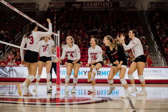 South Dakota outside hitter Sami Slaughter celebrates a point with her teammates.