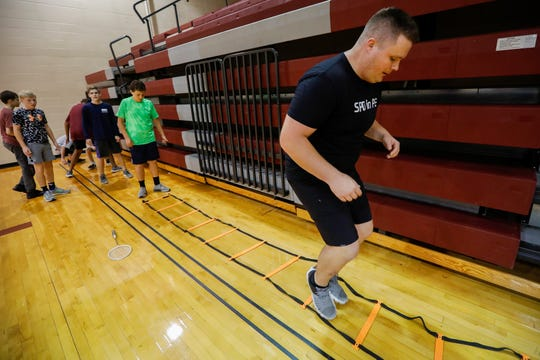 Springfield Police Officer Keith Wright runs through the ladder exercise with seventh-graders at Cherokee Middle School as part of the SPD in PE program on Wednesday.