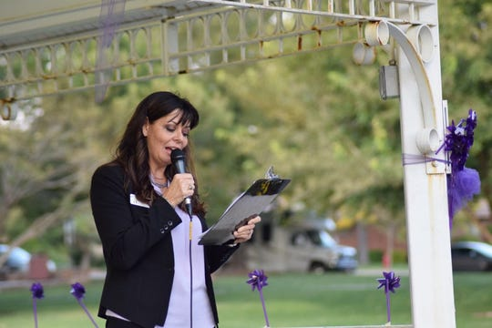 Shonie Christensen, board member for the DOVE Center, reads the story of a local domestic violence survivor, who chose to remain anonymous during a candlelight vigil in St. George last week held to mark Domestic Violence Awareness Month.