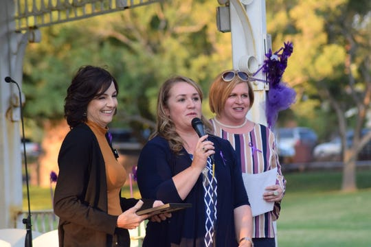Representatives from Cherished Families speak after accepting an award during an event at Vernon Worthen Park in St. George marking this month as Domestic Violence Awareness Month.
