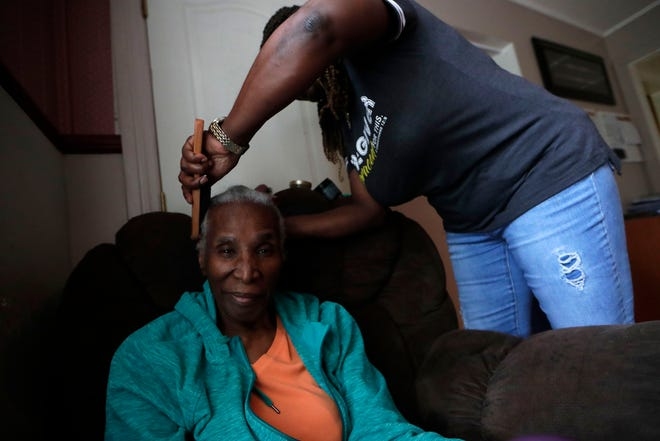 Vera Johnson, who was diagnosed with Alzheimer's in 2015, smiles as her daughter Priscilla Jean-Louis brushes her hair. Jean-louis moved in with her mother after her diagnosis to be her caregiver.
