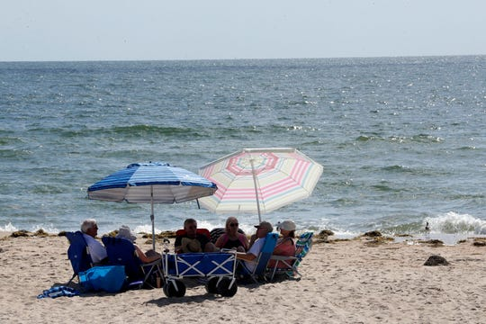 A group of beach goers chat under umbrellas on St. George Island on Saturday, Oct, 12, 2019.
