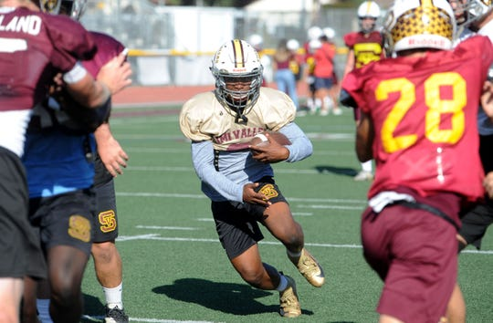 Senior Ranell White, who came to Simi Valley High from Illinois, looks for a hole to run through during the Pioneers' practice Tuesday. Simi Valley plays at Oak Park on Friday night in a Canyon League opener.