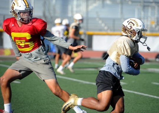 Sophomore quarterback Travis Throckmorton, left, hands the ball off to senior Ranell White during Simi Valley's practice Tuesday. The transfers are two big reasons the Pioneers take a five-game winning streak into Friday night's showdown against Oak Park.