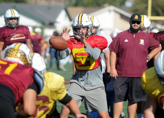 Sophomore quarterback Travis Throckmorton takes a snap during Simi Valley's practice Tuesday. The Pioneers play at unbeaten Oak Park in a Canyon League clash Friday night.