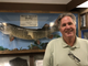 Emmett Brown Jr., the executive director of the Fresh Water Fishing Hall of Fame. Behind him is a recreation of the mount of Spray's muskie. The original mount was destroyed in a fire.