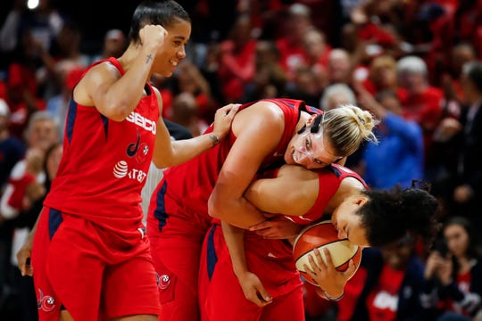 Washington Mystics guard Natasha Cloud, left, forward Elena Delle Donne and guard Kristi Toliver celebrate during the second half of Game 5 of basketball's WNBA Finals, Thursday, Oct. 10, 2019, in Washington.