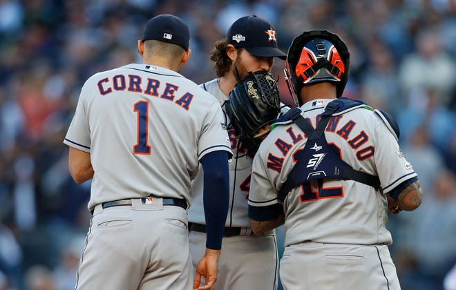 Gerrit Cole talks with Carlos Correa and Martin Maldonado during the first inning.