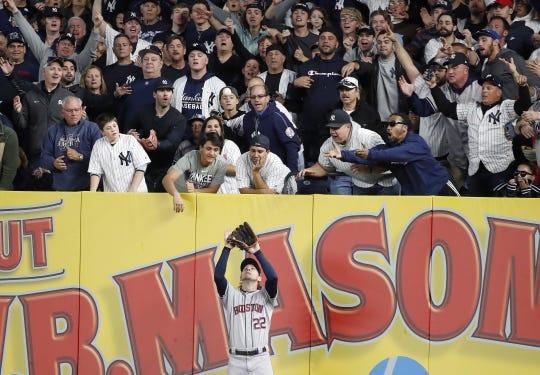 Yankee fans jump on Astros right fielder Josh Reddick as he makes a catch.