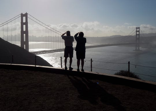 In this 2016 photo, tourists take souvenir photos of San Francisco and its iconic Golden Gate Bridge. Increasingly, residents of this Bay Area city are finding its cost of living too high, forcing them to move out of town and out of the state, returning largely as tourists.