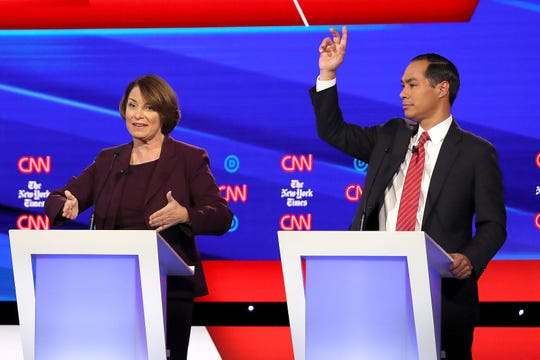 Sen. Amy Klobuchar, D-Minn, and Julian Castro react on stage during the Democratic presidential primary debate at Otterbein University.