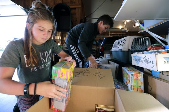 Macy Hartjes, 12, left and Gavin Wiese, 11, sort out donated food items for the St. Joseph Food Program on Oct. 16. The two kids have started a local food drive collecting canned goods with binds outside their homes.