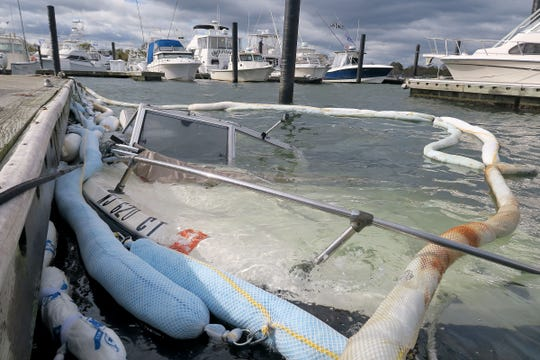 Containment booms surround a boat that sits on the bottom of the Shark River Thursday, October 17, 2019, after it sank at the Belmar Manutti Municipal Marina.  Heavy winds and waves are battering the boats at the marina.