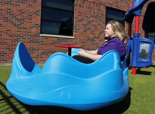 Alyssa Butler, a sophomore from Duncanville, takes a spin on a playground piece outside the Houston-Lantrip Center for Literacy and Learning on Thursday, after the facility's dedication. The playground is designed to accommodate children with special needs.
