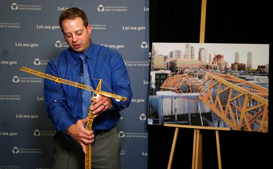 Brian Haight, crane program manager for Washington state's Department of Labor and Industries, uses a model of a crane to explain how a crane can become unstable after pins are removed and high winds come up as he talks about a crane collapse in Seattle months earlier that killed four/ The photo behind him shows broken off sections from the collapse.