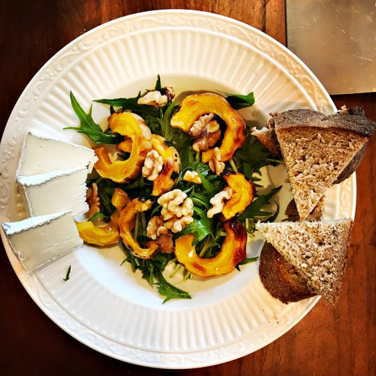 Roasted delicata squash served atop a salad with tangy cheese and bread makes for a delicious fall meal.