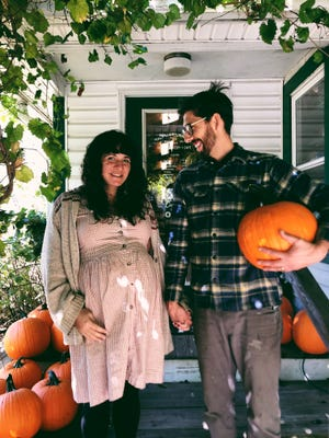 Owners of the Half Moon Market, Demetria and Justin Honeywell, stand outside of the organic food store on Ridgeway Avenue.