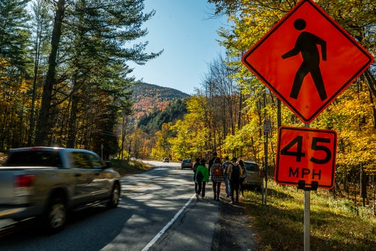 Hikers walk down Route 73 to the Roaring Brook trailhead in St. Huberts, NY, on Saturday, Oct. 12, 2019, past a temporary speed-limit sign put in the place by the Department of Environmental Conservation as part of Columbus Day weekend plans to manage the high number of hikers coming to the High Peaks region of the Adirondack Park.