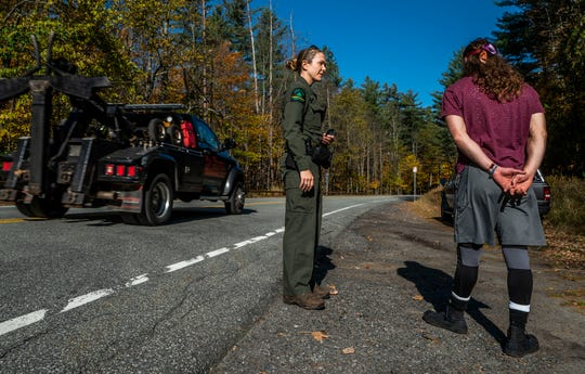 New York Forest Ranger Megan McCone talks with a motorist as a tow truck rolls buy on on Saturday morning, Oct. 12, 2019, informing him that his truck is in a no-parking zone on Route 73 near the Roaring Brook trailhead lot in St. Huberts which was full by 6 a.m. She politely warned at least six drivers within 10 minutes who attempted to park in the same spot that they risked getting a ticket or even being towed.