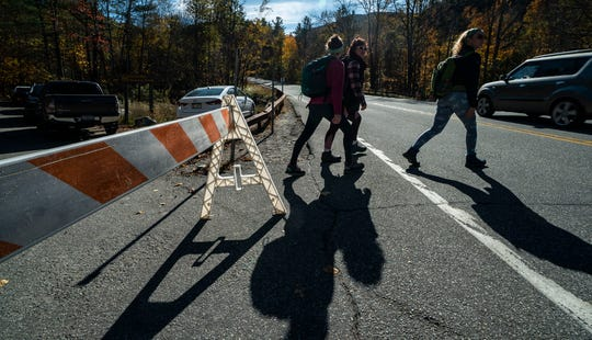 Hikers hurry across Route 73 in St. Huberts, NY, from the Roaring Brook parking area on Saturday, Oct. 12, 2019. The Department of Environmental Conservation instituted a temporary 45 mph speed limit, increased law enforcement, and other measures to help better manage the high volume of people coming to the High Peaks region of the Adirondack Park.