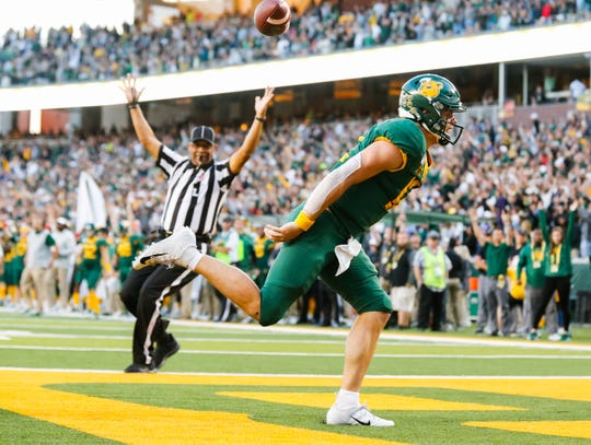 Oct 12, 2019; Waco, TX, USA; Baylor Bears quarterback Charlie Brewer (12) flips the ball in the air after scoring a touchdown in during the first overtime against the Texas Tech Red Raiders at McLane Stadium. Mandatory Credit: Ray Carlin-USA TODAY Sports