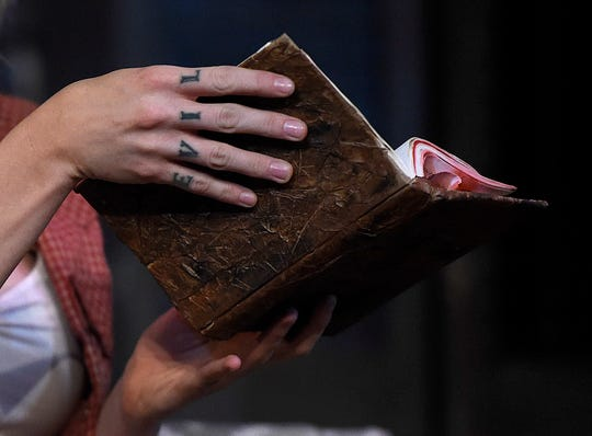 """Emily Thyme has """"evil"""" tattooed on her hands during the """"Evil Dead the Musical"""" rehearsal, Wednesday, Oct. 16, 2019, at Harbor Playhouse. The musical is a rock show based off the cult classic films The Evil Dead, Evil Dead 2 and Army of Darkness."""