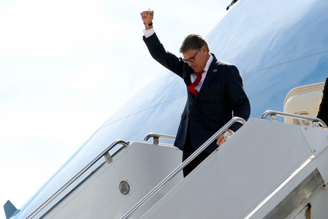 Energy Secretary Rick Perry gestures as he arrives on Air Force One with President Donald Trump at Naval Air Station Joint Reserve Base in Fort Worth, Thursday, Oct. 17, 2019.