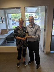 Annette Glendon gives the bottle of Sweet Hickory Rye whiskey to fine spirits specialist Joseph Hyman for bidding.