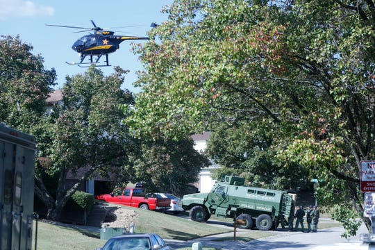 The Hamilton County Police Association SWAT team parks in the driveway while a helicopter flies above a house at the corner of Greenmount and Melissaview in Green Township on Oct. 17, 2019.