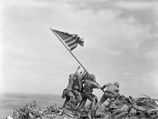 In this Feb 23, 1945, file photo, U.S. Marines of the 28th Regiment, 5th Division, raise the American flag atop Mt. Suribachi, Iwo Jima, Japan. The Marine Corps has corrected the identify of another of the men who were photographed raising the flag. Cpl. Harold P. Keller is mostly obscured behind the Marine second from right, the Marines now say.